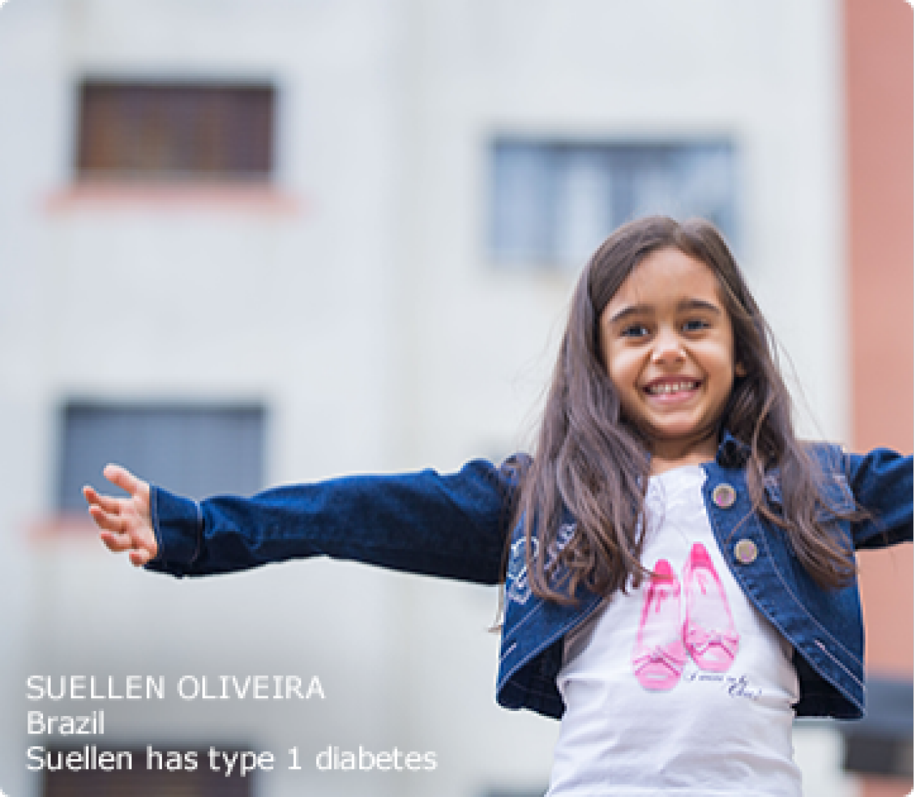 Young type 1 patient (Suellen) standing outside with arms raised