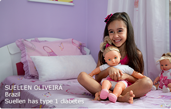 Young type 1 patient (Suellen) sitting on bed and holding a doll