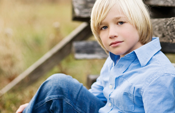 Boy sitting in a field looking at the camera
